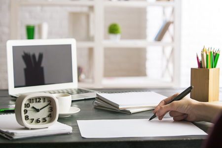 working office: Close up of female writing in notepad placed on wooden desktop with blank laptop, supplies and other items. Mock up Stock Photo
