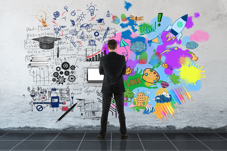 Creative and analytical thinking concept. Back view of businessman looking at concrete wall with colorful sketch and formulas. 3D Rendering Stock Photo