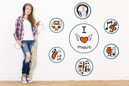 girl in love: Pretty young girl listening to music in interior with sketch on brick wall. I love music concept Stock Photo