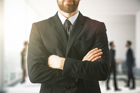 Close up of businessman with folded arms on blurry office background. Worker concept