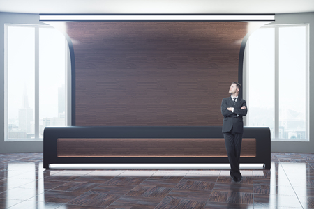 office furniture: Businessman standing at stylish wooden reception desk in interior with city view and sunlight. Mock up, 3D Rendering Stock Photo