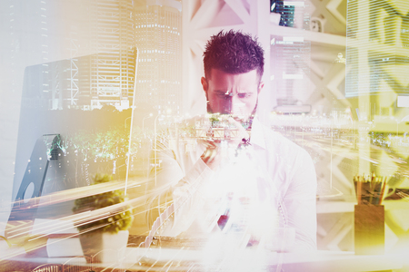 office desk: Pensive young businessmanat workplace with abstract bright city background. Double exposure Stock Photo