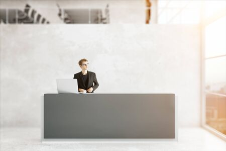 toned: Thoughtful young businessman standing at reception desk of modern loft office. 3D Rendering. Toned image