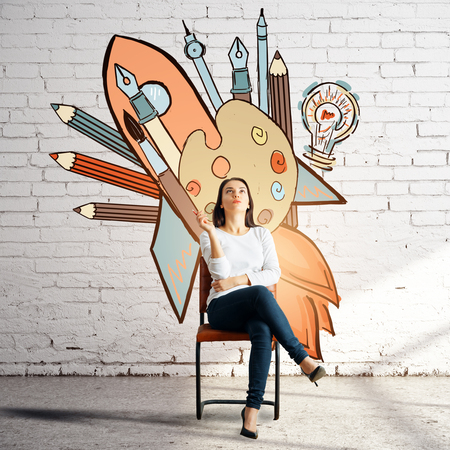 Thoughtful woman sitting on chair in white bricj room with creative sketch on wall. Creativity concept Stock Photo
