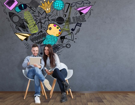 attractive woman: Attractive young man and woman sitting on chairs and using laptop together in room with social media sketch. Communication concept Stock Photo