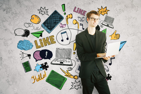 online: Young businessman using laptop on concrete background with bright drawings. Social media concept