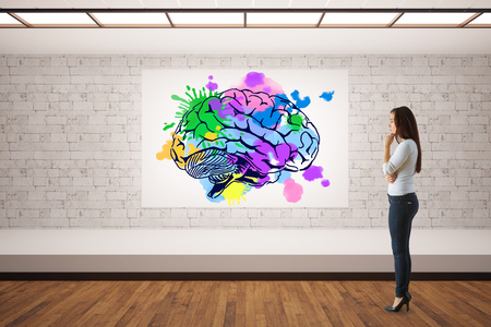 the mind: Attractive thoughtful young woman looking at poster with colorful brain sketch in white brick interior. Creative mind concept. 3D Rendering Stock Photo