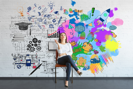Thoughtful young woman sitting on chair in brick interior with colorful sketch on wall. Creative and analytical thinking concept