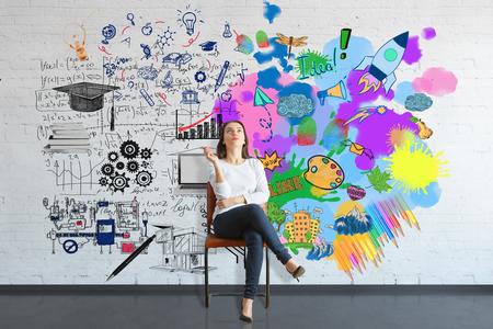 Nachdenkliche junge Frau sitzt auf Stuhl in Backstein-Interieur mit bunten Skizze an der Wand. Kreatives und analytisches Denken Konzept Standard-Bild