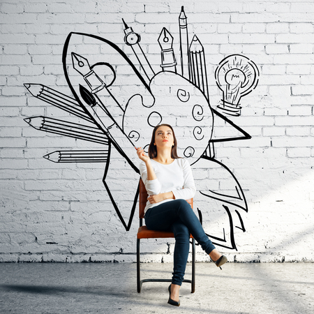 Thoughtful woman sitting on chair in white bricj room with creative sketch on wall. Art concept