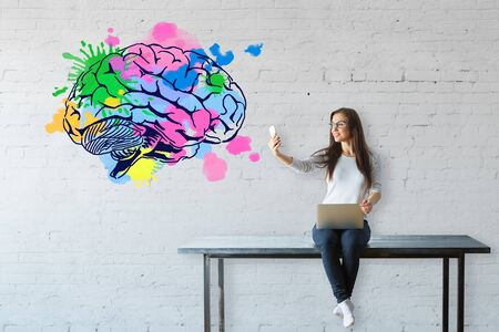 using smartphone: Young woman sitting on table, using laptop and taking selfie with smartphone on white brick background with colorful brain sketch. Brainstorm concept