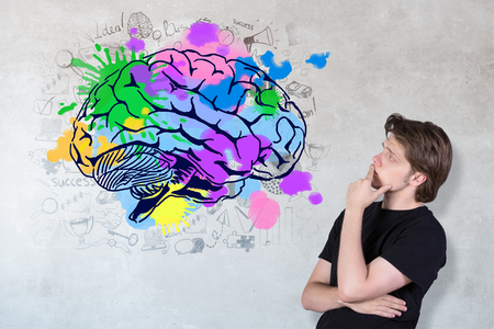 looking at view: Side view of thoughtful young man looking at creative brain sketch on concrete background. Brainstorming concept