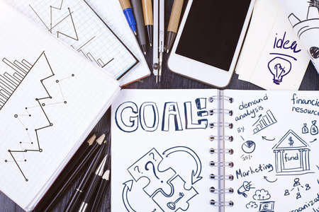 action fund: Top view of messy desktop with sketches, supplies, blank smartphone and other items. Goal concept