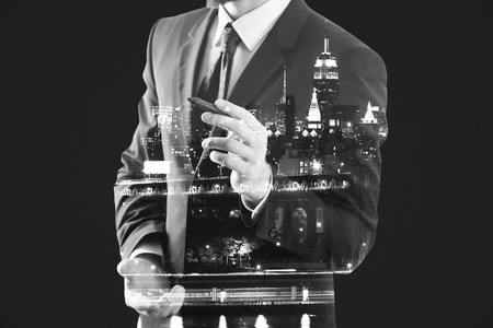 architect drawing: Guy in suit drawing something on abstract city background. Art concept. Double exposure