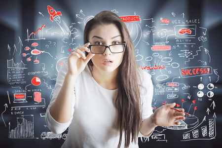 idea: Portrait of surprised young european woman with glasses on blurry background with business doodles. Education concept