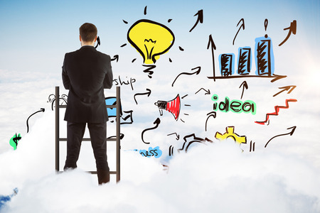 Back view of young businessman standing on top of ladder and looking at creative colorful sketch on sky background. Success concept Stock Photo