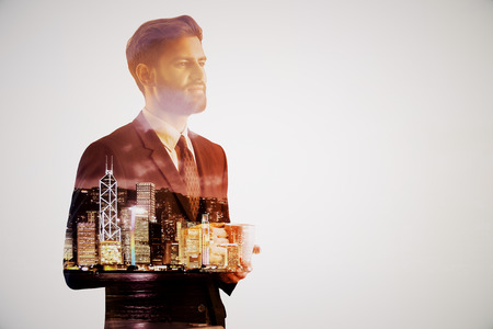 illuminated: Handsome thoughtful young businessman drinking coffee on abstract night city background. Employment concept. Double exposure