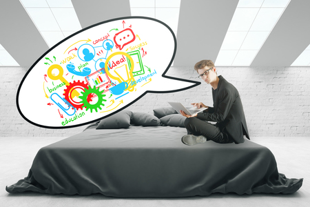 young business man: Young european man with laptop and business sketch in speech bubble sitting on bed in grey interior. Communication concept. 3D Rendering Stock Photo