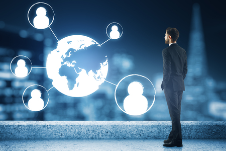 Young businessman on concrete rooftop with night city view, abstract digital HR icons and globe. Network concept Stock Photo