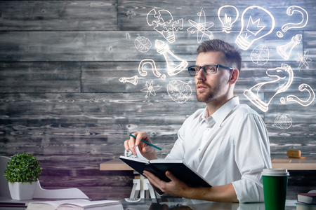 lamp light: Attractive young man writing in notepad at workplace with coffee cup, supplies, other items and creative sketch. Leadership concept Stock Photo