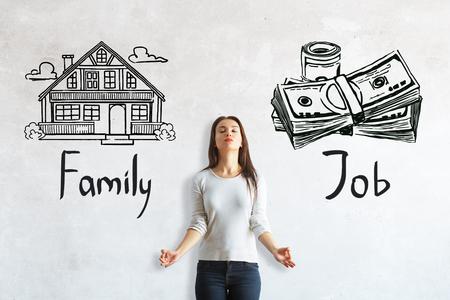 Meditierende junge europäische Frau auf konkretem Hintergrund mit Haus- und Geldskizze. Wahl zwischen Arbeit und Familie