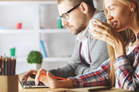 working office: Side view of young european male and female in modern office working on project together Stock Photo