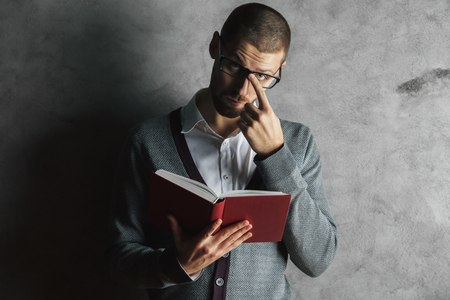 book: Portrait of attractive young man reading book on concrete background. Education concept Stock Photo