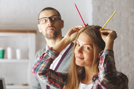 european: Portrait of attractive european man and woman playing with supplies at workplace. Break concept Stock Photo