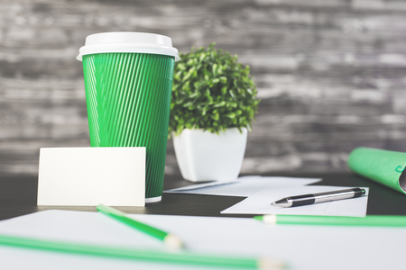 Close up of green take away coffee cup and blank business card on wooden desk with plant and supplies. Mock up