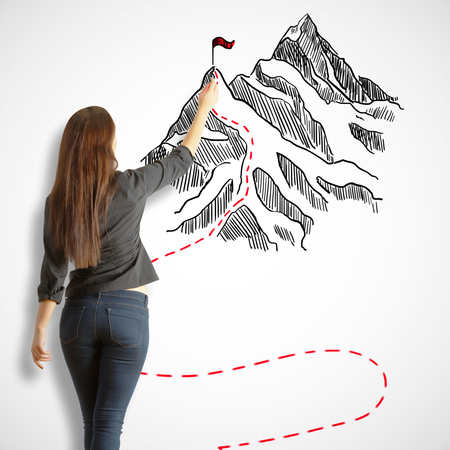 Back view of young woman drawing mountains with flag on white background. Leadership concept
