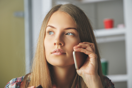 Portrait of attractive thoughtful woman talking on the phone in modern office. Communication concept Stock Photo