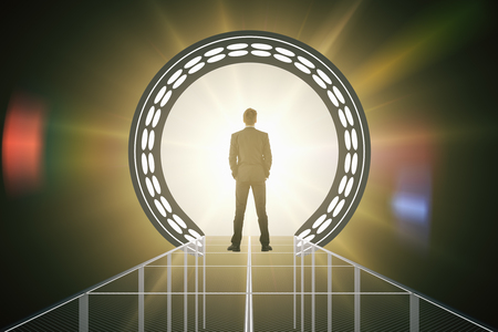 Back view of businessman standing in front of abstract amber teleport with bright light. 3D Rendering Stock Photo