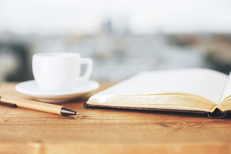 Close up of wooden desktop with notepad, coffee cup and other items. Blurry city background