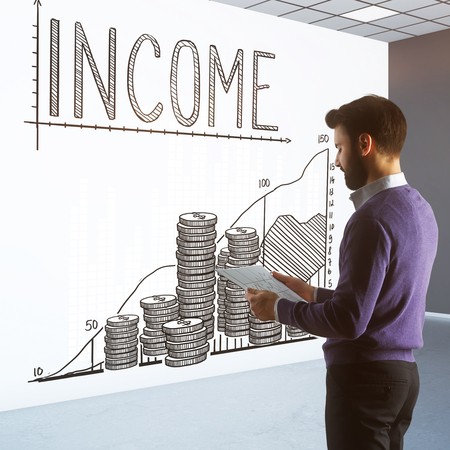 Thoughtful young man in interior with creative money chart sketch on wall. Earnings concept