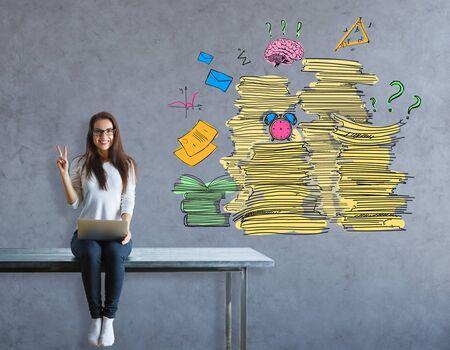 Vrolijk jong europees meisje zittend op tafel en toont vredesteken op concrete achtergrond met papierwerk stapels. Werkbelastingconcept Stockfoto
