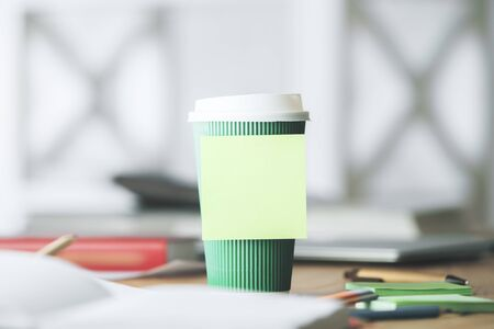 table top: Close up of blank sticker on green coffee cup, colorful supplies and other blurry items. Mock up