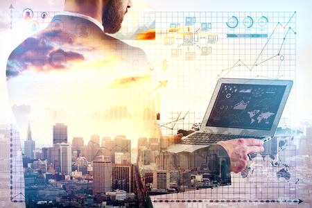 Young businessman using laptop on city background with business charts and graphs. Technology concept. Double exposure