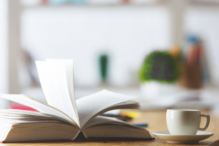 book: Close up of wooden office desktop with ceramic coffee cup, open book, blurry plant, supplies and other items. Education concept Stock Photo