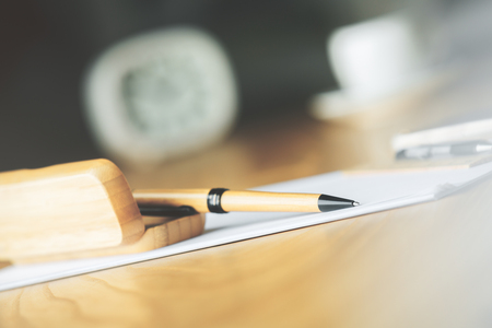 Close up of brown pen with wooden case on desktop with blurry clock and coffee cup Stock Photo