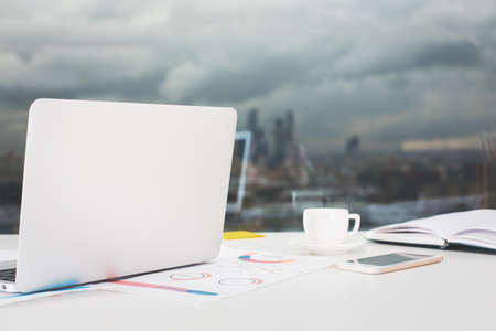Close up of open laptop, financial reports, smartphone and coffee cup placed on windowsill with dull city view Stok Fotoğraf