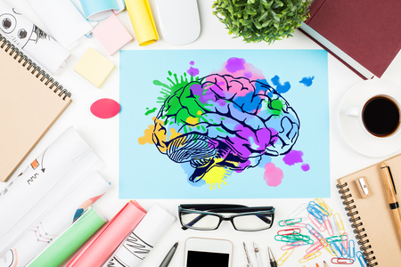 power of thinking: Top view of messy office desktop with coffee cup, supplies and colorful brain sketch. Creative mind concept Stock Photo