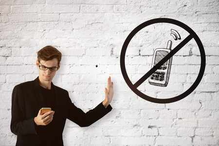 despite: European guy on white brick background using cellphone despite the inhibitory sign. Addiction concept