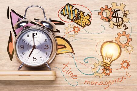 working hours: Close up of silver alarm clock on wooden shelf. Creative business drawings in the background. Time management concept