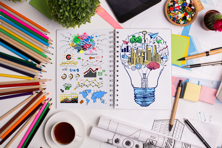 Top view of white office tabletop with colorful business sketch, supplies, electronic devices and other items. Success concept Archivio Fotografico