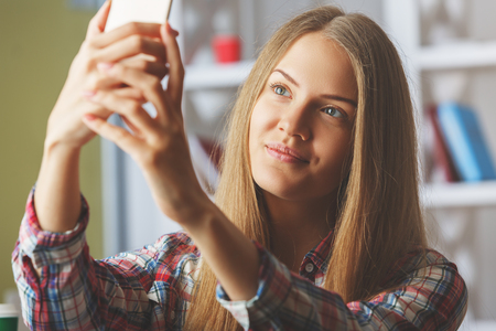 Smiling young blonde lady taking selfie with cellphone