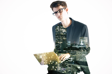 electronic: Side view of young man using laptop on abstract city background. Double exposure