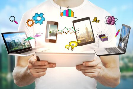 using tablet: Young businessman using abstract devices with drawings on blurry landscape background. Digital business concept