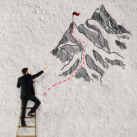 profession: Back view of young man on ladder drawing mountains with flag on white background. Winning concept Stock Photo