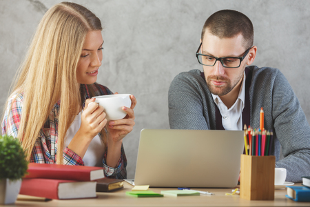 european: Young european man and woman in modern office working on project together