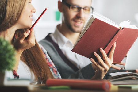 european: Portrait of attractive european boy and girl reading books in modern office. Education and knowledge concept